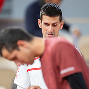 PARIS, FRANCE October 03. Novak Djokovic of Serbia and Daniel Elahi Galan of Colombia check the clay surface after a rain delay during the third round of the singles competition on Court Philippe-Chatrier during the French Open Tennis Tournament at Roland Garros on October 3rd 2020 in Paris, France. (Photo by Tim Clayton/Corbis via Getty Images)