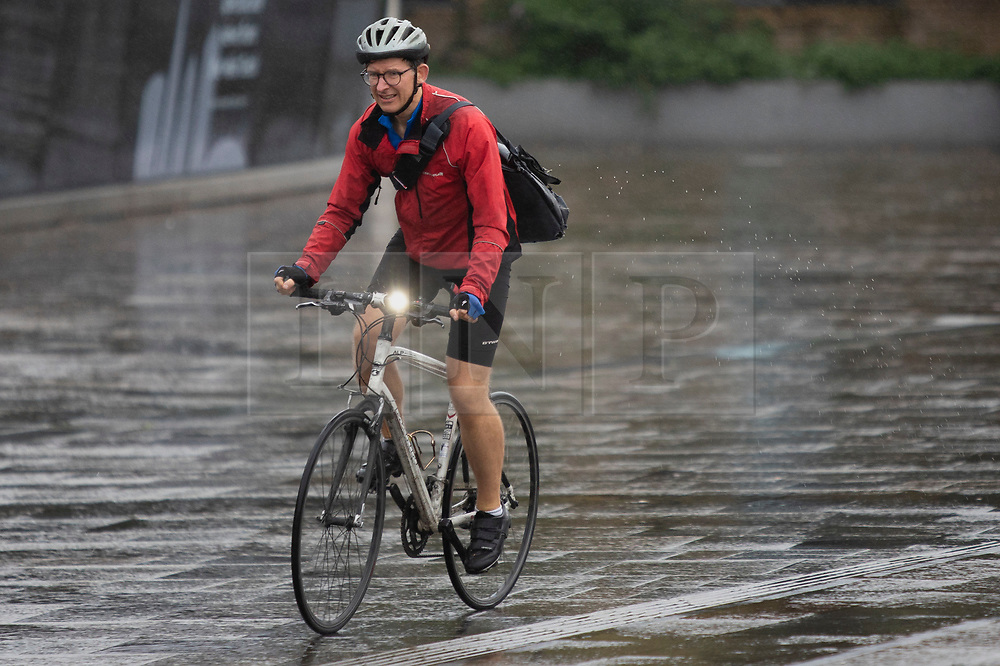 © Licensed to London News Pictures. 27/09/2021. London, UK. A man cycles during a rain shower in Greenwich, South East London. Rain showers are forecasted to continue in parts of London and South East England for the rest of the week.  Photo credit: George Cracknell Wright/LNP