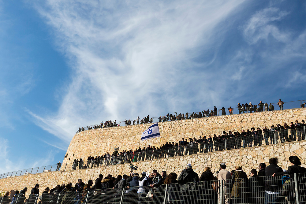 Friends, relatives and other members of the Jewish community gather for the burial ceremony as they attend the joint funeral of four Jewish victims of the terrorist attack on a kosher grocery store in Paris last week, at Givat Shaul cemetery in Jerusalem, Israel, on January 13, 2015. Thousands of mourners attended the funeral of Yohan Cohen, Philippe Braham, Francois-Michel Saada and Yoav Hattab, the four French Jews killed in the attack, after their bodies of were flown to Israel from France for burial in the Jewish state.