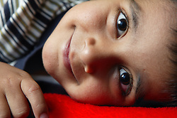 Portrait of young boy lying down smiling,