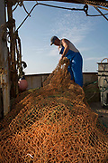 A fisherman repairing the nets on his boat before going out trawler fishing, Folkestone Harbour, Folkestone, Kent, United Kingdom.