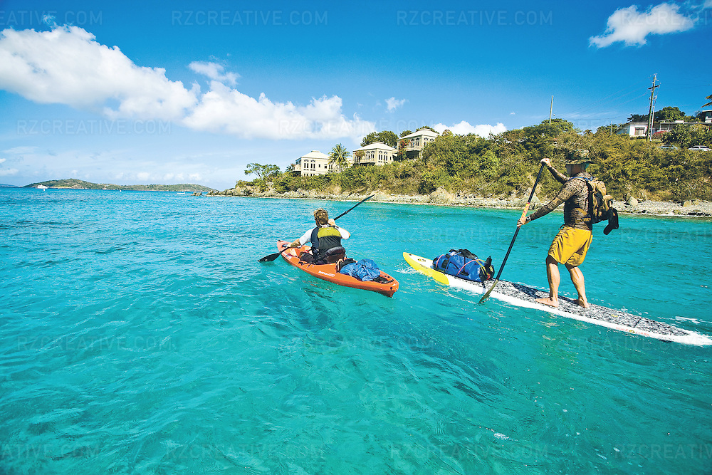 Two men paddle a sit-on-top kayak and standup paddleboard near Cruz Bay on the island of St. John, part of the U.S. Virgin Islands.