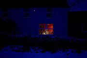 A Christmas tree glows in a warm window of a rural house seen from outside in bleak temperatures during mid-winter snows in England. In deep blue light we experience from the feel of this picture, the rawness of deep winter, the icy conditions where an unseen country-living family are safe indoors. The property is a cottage on a quiet road in the Mendip hills, southeast of the city of Bristol in western England. It is during the Christmas holiday period and families, who are lucky to have reached their homes during very difficult weather, are now enjoying the solitude and tranquillity of a peaceful life - away from the metropolis. Their brick wall is topped with snow and the light from the burglar alarm shows the security system is active
