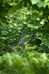 Looking towards the statue of Dionysus in the Nuttery at Sissinghurst Castle Garden in summer