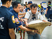 30 AUGUST 2016 - BANGKOK, THAILAND:  Volunteers help a man balance a basket of food and clothing at the Poh Teck Tung shrine on the last day of Hungry Ghost Month in Bangkok. Chinese temples and shrines in the Thai capital host food distribution events during Hungry Ghost Month, during the 7th lunar month, which is usually August in the Gregorian calendar.         PHOTO BY JACK KURTZ