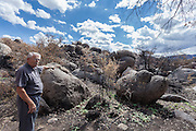 Doug Camblin points out damage from the Yarnell Hill Fire in the rocks surrounding Carraro's Gratto in Yarnell, Arizona.