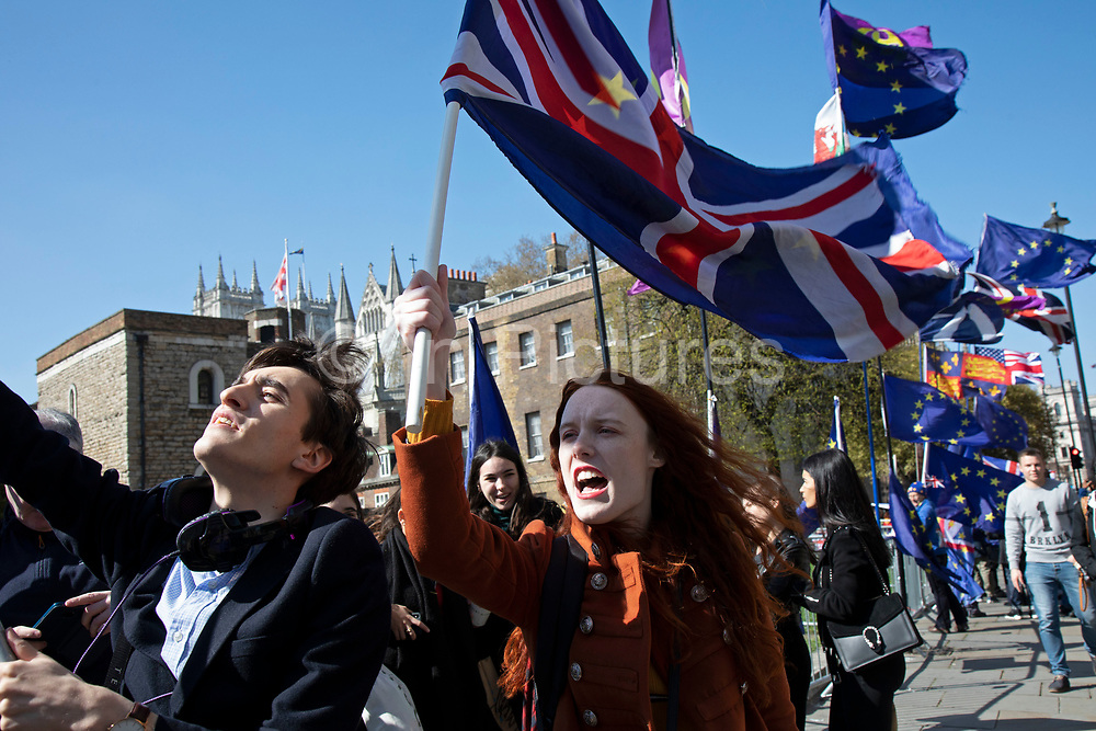 Young anti Brexit protesters Shaun Smith-Milne, from Liverpool and Florine Pochet from Lille in France shout anti-Brexit slogans and wave flags opposite Parliament in Westminster as the Prime Minister arrives in Brussels to request an extension to Article 50 so the UK can continue to try to agree a Brexit Withdrawal Agreement on 10th April 2019 in London, England, United Kingdom. With just two days until the UK is supposed to be leaving the European Union, the delay decision awaits.