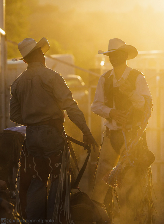 Two cowboys in the backlit dust before a rodeo