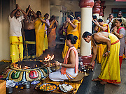 27 DECEMBER 2015 - SINGAPORE, SINGAPORE: Hindu priests lead a religious service at the Sri Mariamman temple in Singapore. The Sri Mariamman Temple is Singapore's oldest Hindu temple. It is an agamic temple, built in the Dravidian style. The temple is in the downtown Chinatown district, and serves Hindu Singaporeans and Tamilians. Due to its architectural and historical significance, the temple has been gazetted a National Monument and is a major tourist attraction. The Sri Mariamman Temple was founded in 1827 by Naraina Pillai, eight years after the East India Company established a trading settlement in Singapore.       PHOTO BY JACK KURTZ