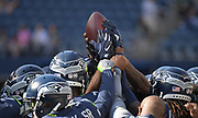 Aug 25, 2017; Seattle, WA, USA; Seattle Seahawks players hoist a football and join hands in a huddle during a NFL football game against the Kansas City Chiefs at CenturyLink Field.
