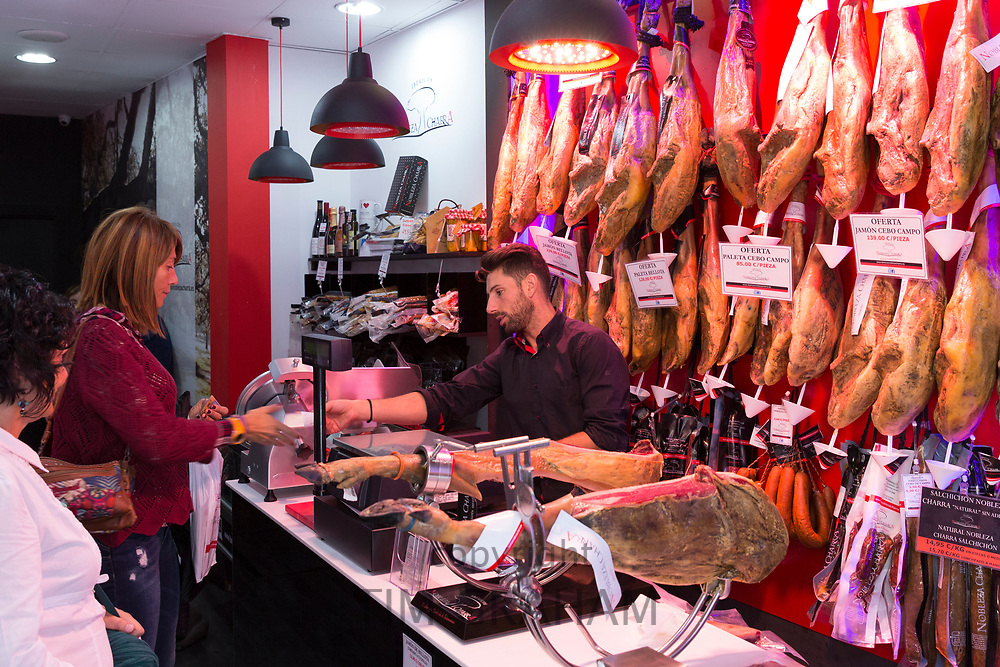 Women buying Iberico Jamon specialty Spanish ham in butcher shop in old town Salamanca, Spain