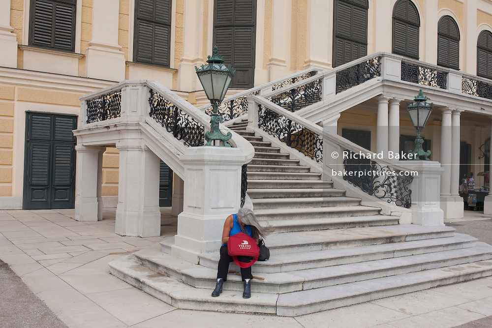 Woman tourist on the steps at Schloss Schonbrunn, in Vienna, Austria, EU.
