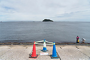 family at Tokyo Bay water edge with swimming warning sign, Umikaze park, Yokosuka with Sarushima Island