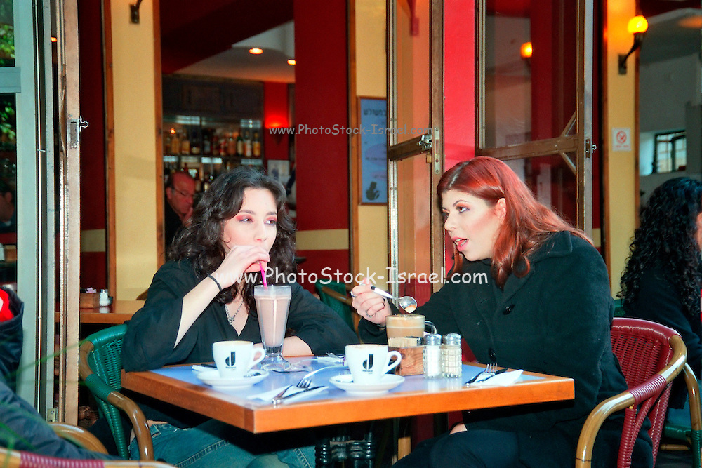 Israel, Tel Aviv, Two teens ordering breakfast in an open air restaurant