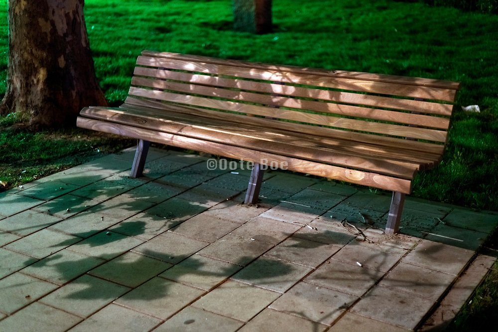 wooden bench with leaves shadow during night in a urban public park