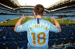 A Manchester City fan with 'Champions 18' on his back before the game