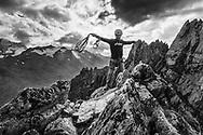 Ein Kletterer nimmt auf dem Gipfel des Pfriendlers vor dem Abseilen das Seil zusammen, Susten, Berner Oberland, Schweiz<br /> <br /> A climber is preparing the rope for the abseiling on the peak of the Pfriendler, Susten, Bernese Oberland, Switzerland