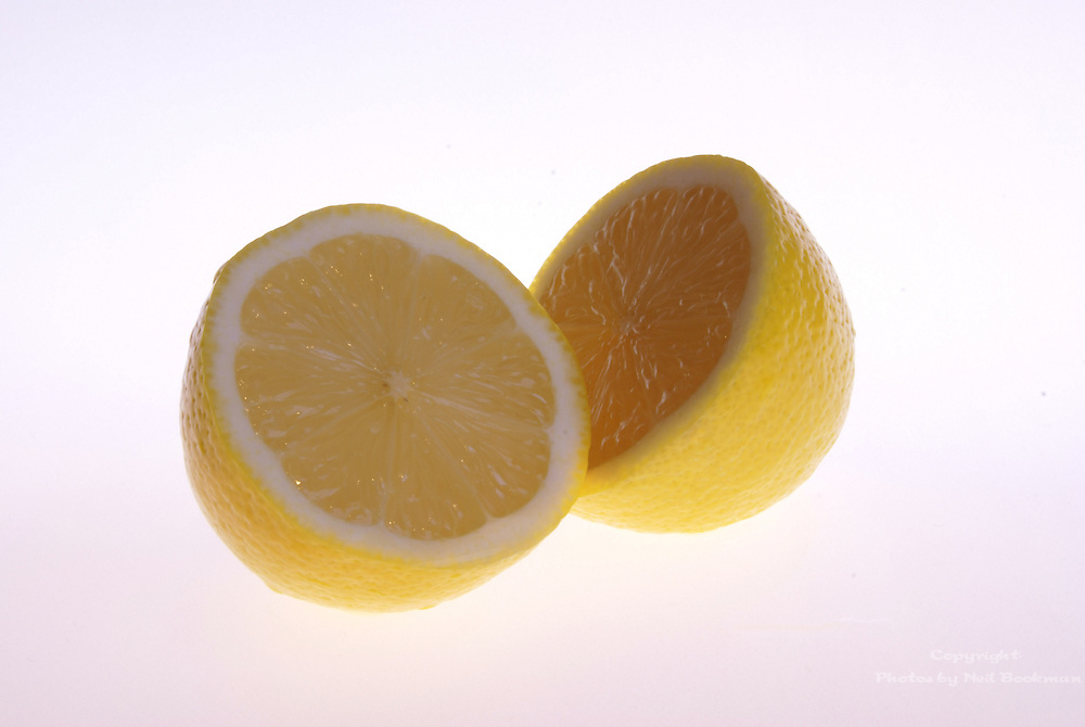 A lemon sliced in half on a white background.