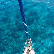 Sunlight glistens on a clear blue ocean, seen from the height of a sailboat's mast.