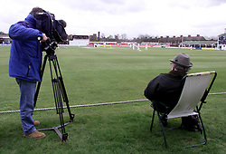 A spectator and a cameraman watch the first day of Leicestershire's County Championship match against Essex at Grace Road, Leicester.