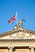 Union Jack flag flying with britannia holding scales of Justice on top of the Guildhall building, Bath, Somerset, England