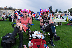 © Licensed to London News Pictures.22/08/15<br /> Castle Howard, North Yorkshire, UK. <br /> <br /> BECKY GARBUTT (L) and DEBBIE CLAYTON wave their flags as they join hundreds of other people attending the 25th anniversary of the Castle Howard Proms event near York. The theme of the event this year is a commemoration of the 75th anniversary of the Battle of Britain and the 70th anniversary of VE day and brings an evening of classic musical favourites celebrating Britishness to the lawns of Castle Howard.<br /> <br /> Photo credit : Ian Forsyth/LNP