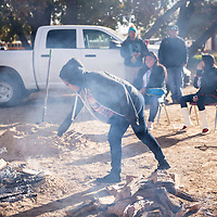 Keena Francisco, 14, a freshman at To'hajiilee Community School, adding wood to Over 30 turkeys were cooked in the ground during the annual turkey-in-the-hole celebration at To'hajiilee Community School, Tuesday, Nov. 20, in To'hajiilee.