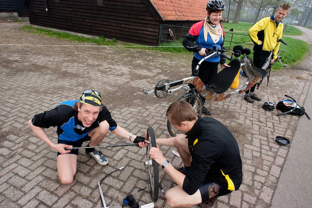 Tijdens de toertocht met het Paastreffen moet een lekke band van een tandem worden geplakt.<br /> <br /> During a tour with the Dutch Society of Human Powered Vehicles, one of the participants is being helped with a flat tyre on the tandem.