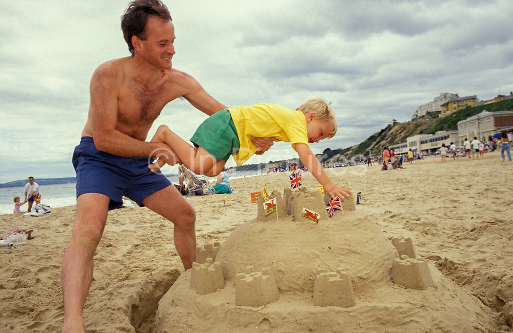 A dad holds his son over their sandcastle, for the boy to plant his Union Jack and Welsh Dragon flags at the top, during their holiday at Bournemouth, on 20th October 1990, in Bournemouth, England.