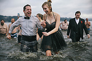 Scott Provence, left, Jo Landis, and Collin Provence, right, are dressed to the nines as they and several hundred other brave souls participate in the 15th annual Matthews Beach Polar Bear Plunge, Sunday, Jan. 1, 2017.