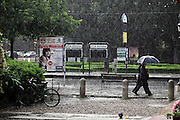 two people walking while a heavy rain falls down