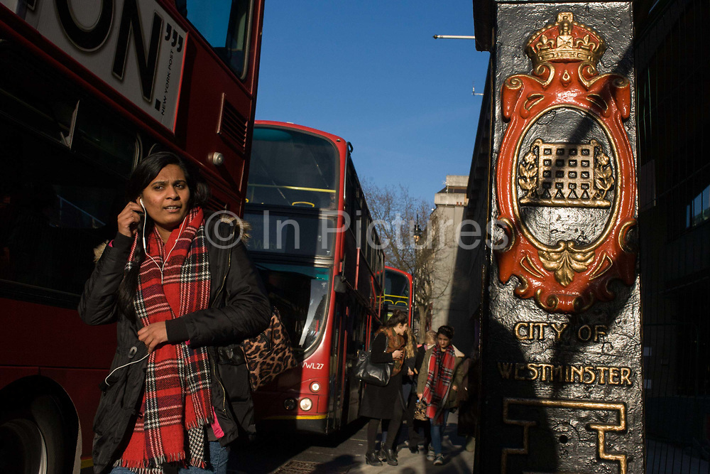 Seen from a low angle, late afternoon pedestrians walk into bright sunlight on the Strand in central London. A young woman of south Asian descent wears a tartan scarf, plugs he earphone into her ears During roadworks that have disrupted pedestrian and traffic access along this busy street, cyclists and walkers share urban space. The woman's scarf pattern echoes that of the portcullis gate emblem that stands for the borough of Westminster is seen on a post on the right.