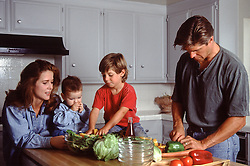 family of four cooking together in the kitchen
