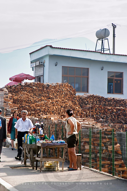 Street scene: Street merchants selling bottles of motor oil, soft drinks, Coca Cola and other things in front of a big stockpile of fire wood. Tirana capital. Albania, Balkan, Europe.