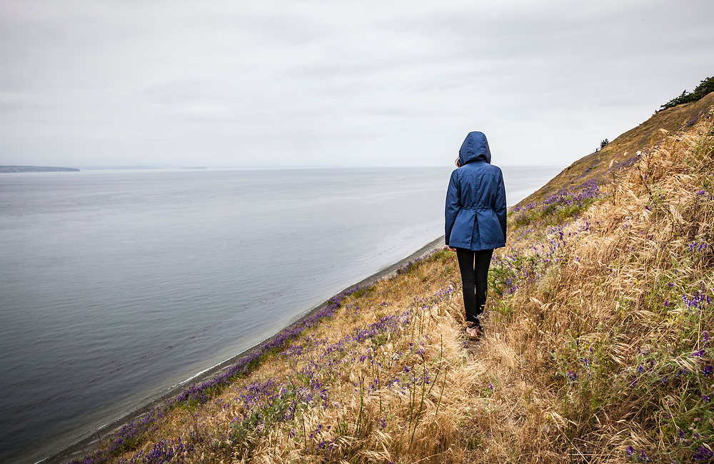 A lone hooded figure / young woman on Ebby Bluff, Ebey's Landing National Historical Reserve, Whidbey Island, Washington, USA.