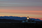 The West Point Light, also known as the Discovery Park Lighthouse, shines as a winter sunset colors the sky above the Olympic Mountains in Washington state. West Point Light was the first manned light station on Puget Sound and was activated on November 15, 1881. It is located in Discovery Park, Seattle, Washington.