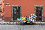 A Mexican balloon seller carries her wares on a pole through the streets of San Miguel de Allende, Mexico.