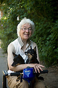 Elderly lady with her dogs in mobility vehicle, UK