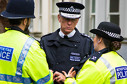 London, August 31st 2015. Met Police Commissioner Sir Bernard Hogan-Howe chats to police officers as revellers ignore the inclement weather to enjoy day two of the Notting Hill Carnival.