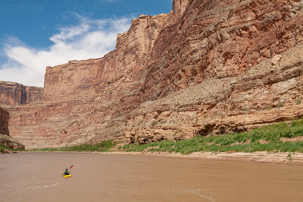A paddler in a yellow playboat paddles a calm section of the Colorado River in Cataract Canyon — a 46 mile long canyon located within Canyonlands National Park and Glen Canyon National Recreation Area in southern Utah. Photo © Robert Zaleski / rzcreative.comPhoto © Robert Zaleski / rzcreative.com<br /> —<br /> To license this image for editorial or commercial use, please contact Robert@rzcreative.com