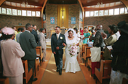 Man and woman walking down church isle arm in arm following marriage ceremony,