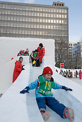 Children using snow slide in Odori Park during Sapporo Snow Festival in Japan
