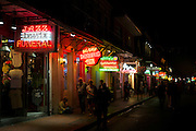Jazz funeral, daiquiris and pizza on offer among signs in famous Bourbon Street in French Quarter of New Orleans, USA