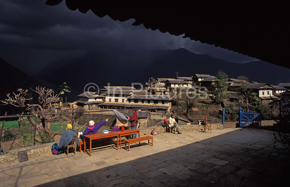 Trekkers sit in morning sunshine on the terrace of their guesthouse as gathering dark clouds approach the Himalayan village of Ghandrung, on 12th December 1997, In Ghandrung, Nepal. Also called Ghandruk or Gandruk, this settlement is situated in what is known as the Annapurna Sanctuary conservation region, a 55-km-long massif whose highest point, Annapurna I, stands at 8,091 m 26,538 ft, making it the 10th-highest summit in the world. The village is also a stopping-off point for trekkers and backpackers who pass-by on their way to the walk in high peaks. The Mountain Region is situated at 4,000 meters or more above sea level. Houses and dwellings are substantial structures with properties well-swept and well-maintained.