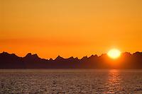 sun setting behind Lofoten Islands and waters of Vestfjord, Norway