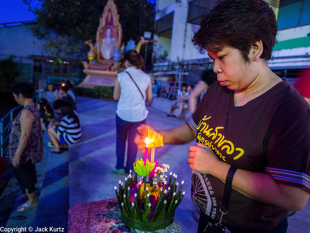 """17 NOVEMBER 2013 - BANGKOK, THAILAND: A woman lights the candle on her krathong before floating it in the Chao Phraya River at Wat Yannawa on Loy Krathong in Bangkok. Loy Krathong (also written as Loi Krathong) is celebrated annually throughout Thailand and certain parts of Laos and Burma (in Shan State). The name could be translated """"Floating Crown"""" or """"Floating Decoration"""" and comes from the tradition of making buoyant decorations which are then floated on a river. Loi Krathong takes place on the evening of the full moon of the 12th month in the traditional and they do this all evening on the 12th month Thai lunar calendar. In the western calendar this usually falls in November. The candle venerates the Buddha with light, while the krathong's floating symbolizes letting go of all one's hatred, anger, and defilements       PHOTO BY JACK KURTZ"""