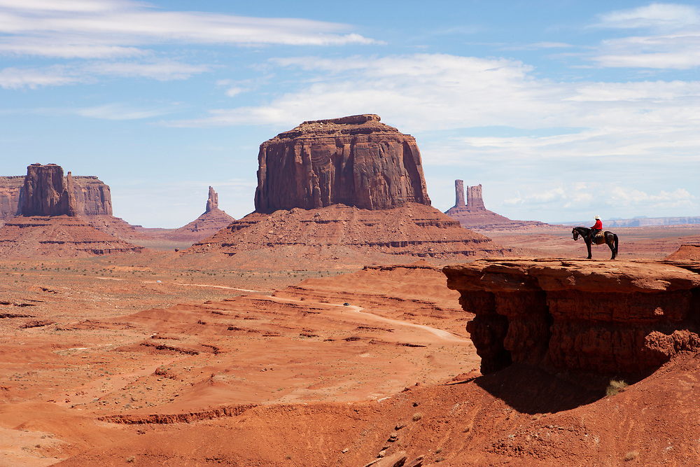 Distant view of lone horseback rider on John Ford Point in Monument Valley Utah