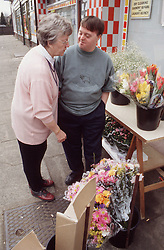 Mother and adult son with Downs Syndrome shopping at florists,
