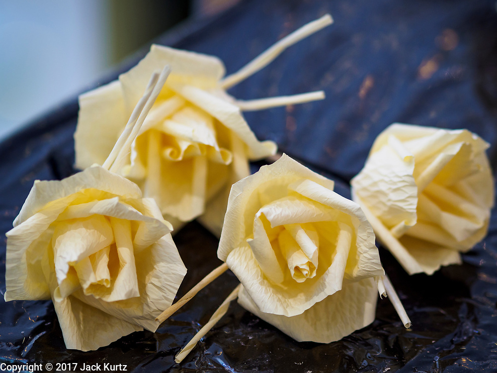 """24 MAY 2017 - BANGKOK, THAILAND: Just completed wooden roses at the Emporium, an upscale shopping mall in Bangkok, the roses will be used during the cremation of Bhumibol Adulyadej, the Late King of Thailand. In Thai culture it is customary to place wooden flowers in front of a deceased person's coffin or urn as a last tribute before cremation. The Royal Cremation Organisation Committee, which is overseeing plans for the cremation of Bhumibol Adulyadej, the Late King of Thailand, asked the Bangkok Metropolitan Administration (BMA) to provide three million wooden flowers for the late King's cremation. The BMA, in turn, has asked malls and civic organizations to provide flowers. The Mall Group, which owns Emporium, has pledged to provide up to one million wooden """"Wiangping"""" roses, which in Thai culture symbolize unconditional love. The late King will be cremated October 26, 2017.     PHOTO BY JACK KURTZ"""