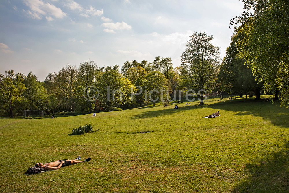 People laying in the warmth of the afternoon sun in Waterlow park during the Coronavirus pandemic on 24th April 2020 in London, United Kingdom. Social distancing measures like this are steps taken to reduce social interaction between people to help reduce the transmission of coronavirus COVID-19. Sunbathing is banned during the crisis and the only time people should be outside is when taking exercise.